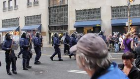 Zamieszka funkcjonariuszi policji z drewnianymi batutami maszerują wpólnie zbiory