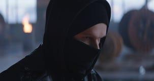 Zamieszka mężczyzna stawia czarnego balaclava w przemysłowym tle 4k, zwolnione tempo zdjęcie wideo