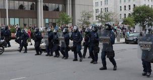 Zamieszki milicyjna linia maszeruje naprzód podczas gdy taktyczna batuta na ich osłonie zbiory