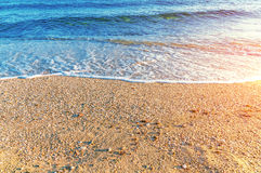 Zamknięta piasek plaża, fala w Grecja z płonącym słońcem i Zdjęcia Stock