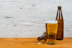 Zamknięte i rozpieczętowane piwne butelki z pełnym szkłem na pubu stole obraz royalty free
