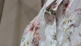 Zamkniętego widoku żeńska bluzka z kwiecistymi wzorami na wieszaku zbiory wideo