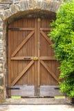 Zamknięty drewniany drzwi na kamiennej ścianie i zieleni drzewie Zdjęcie Stock