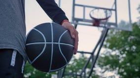Zamknięty materiał filmowy żeńska ręki mienia koszykówka, stoi w parku, obręcz w tle, dzień zdjęcie wideo