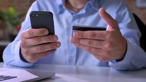 Zamknięty materiał filmowy mężczyzna wręcza płacić rachunki z kredytową kartą, nabywający przez interneta, siedzi przy stołem zbiory wideo
