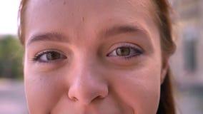 Zamknięty materiał filmowy piękna młoda imbirowa kobieta ono przygląda się patrzejący kamerę, outdoors, dzień zbiory