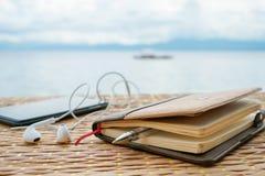 Zamknięty notepad, pióro i telefon z hełmofonami przeciw tropikalnemu morzu pod chmurnym niebem, Obraz Royalty Free