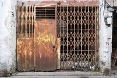 Zamknięty stary wietrzejący ośniedziały metalu drzwi w slamsy okręgu Obrazy Stock