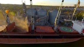 Zamknięty widok ładuje zbożowe uprawy na masowym freighter przez bagażnika otwierać ładunków chwyty przy silosowym terminal w por zdjęcie wideo