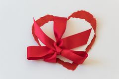 Zamknięty widok czerwonego i białego papieru valentine serca wiążący wraz z czerwonym atłasowym łękiem Zdjęcia Royalty Free