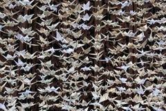 Zamknięty widok 1000 papierowych żurawi rzeźbi przeciw rdzewiejącemu dokonanemu żelazu, origami fotografia royalty free