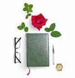 Zamknięty zielony notatnik, szkła, czerwieni róża i zieleń liście, pióro, wristwatch Mieszkanie nieatutowy Skład przedmioty Ty mo Fotografia Royalty Free