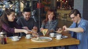 Zamkniętych przyjaciół młodzi człowiecy i kobiety je wyśmienicie jedzenie w dzielą wielką pizzę wygodnej kawiarni i opowiadać prz zdjęcie wideo