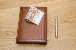 Zamknięty brown luksusowy notepad z balowym piórem i niektóre euro banknotami Zdjęcie Royalty Free