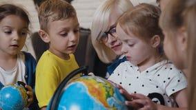 zamknij 4 przyjaciół zabawy dziewczynę Żeński młody nauczyciel i ucznie patrzeje kulę ziemską z powiększać - szkło w geografii sa zbiory wideo