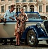 Zamożna para blisko klasycznego kabrioletu przeciw pałac królewskiemu fotografia stock