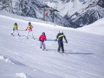 Zams, Austria - 22 Februar 2015: Ski resort. Children with instructor skiing and practicing the correct moves on slope in Alps. royalty free stock photos