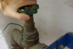 Zamyka faucet - ręki na kole Obraz Royalty Free