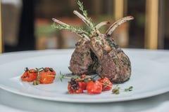 Zamyka od wierzchołka dolny widok grill z ziobro z rozmarynami, solą i zieleniami na restauracyjnym tle, Obrazy Royalty Free