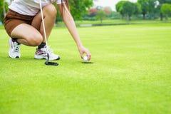 Zamyka piłka żeński golfowego gracza zrywanie w górę piłki Obrazy Stock