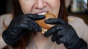Zamyka up ładna dziewczyna je hamburger w kawiarni w czarnych rękawiczkach obraz stock