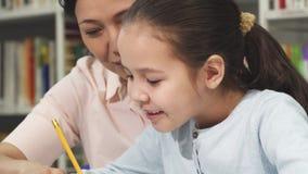 Zamyka up śliczny małej dziewczynki studiowanie z jej matką zbiory wideo