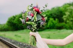 Zamyka up ślubny bukiet z kwiatami i białym faborkiem zieleni, czerwieni i fiołka, Panna młoda z Ślubnym bukietem w ona ręki Fotografia Royalty Free