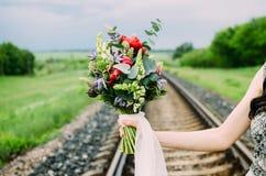 Zamyka up ślubny bukiet z kwiatami i białym faborkiem zieleni, czerwieni i fiołka, Panna młoda z Ślubnym bukietem w ona ręki Zdjęcia Royalty Free