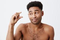 Zamyka up śmieszna ciemnoskóra samiec z afro fryzurą i nagi ciało pokazuje małego znaka z ręką, patrzejący na boku z Zdjęcia Stock