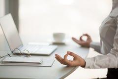 Zamyka up żeński pracownik medytuje w lotosowej pozyci przy pracą fotografia stock