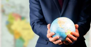 Zamyka up agenta biura podróży mienia kula ziemska przeciw rozmytej mapie Zdjęcie Royalty Free