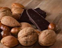 Zamyka up asortowane dokrętki i pices czekolada na drewnianej zakładce Obraz Royalty Free