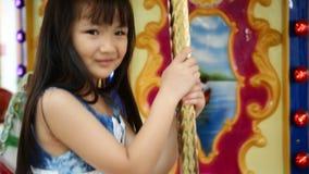 Zamyka up azjatykciego dziecka jeździecki carousel przy karnawałem zbiory