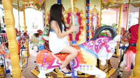 Zamyka up azjatykciego dziecka jeździecki carousel przy karnawałem zbiory wideo