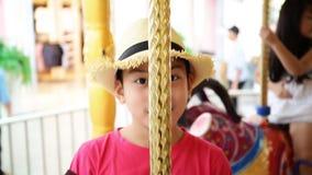 Zamyka up azjatykciego dziecka jeździecki carousel przy karnawałem zdjęcie wideo