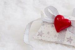Zamyka up biel i osrebrza teraźniejszego pudełko z czerwonym sercem dla chri Obrazy Stock