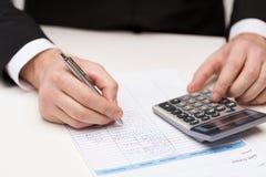 Zamyka up biznesmen z papierami i kalkulatorem zdjęcia stock
