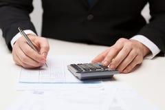 Zamyka up biznesmen z papierami i kalkulatorem fotografia stock