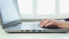 Zamyka up biznesowy mężczyzna pisać na maszynie na srebnym laptopie zbiory