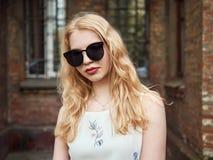 Zamyka up blondynki studencka dziewczyna w modnych okularach przeciwsłonecznych pozuje przeciw ściana z cegieł, cieszący się ciep Zdjęcie Royalty Free