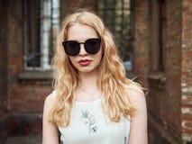 Zamyka up blondynki studencka dziewczyna w modnych okularach przeciwsłonecznych pozuje przeciw ściana z cegieł, cieszący się ciep Zdjęcia Stock