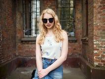 Zamyka up blondynki studencka dziewczyna w modnych okularach przeciwsłonecznych pozuje przeciw ściana z cegieł, cieszący się ciep Obrazy Royalty Free