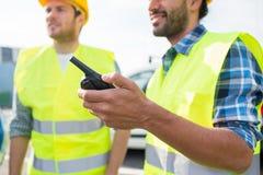 Zamyka up budowniczowie w kamizelkach z walkie talkie Zdjęcia Stock