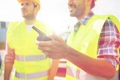 Zamyka up budowniczowie w kamizelkach z walkie talkie Zdjęcia Royalty Free