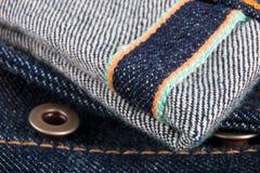 Zamyka up cajgu czerep z guzikiem bawełniana drelichowa szczegółu tkaniny cajgów tekstura selvage Obrazy Stock
