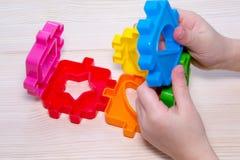 Zamyka up child& x27; s wręcza bawić się z kolorowym plastikowym konstruktorem na drewnianym tle Obrazy Royalty Free