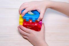 Zamyka up child& x27; s wręcza bawić się z kolorowym plastikowym konstruktorem na drewnianym tle Fotografia Royalty Free