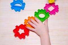 Zamyka up child& x27; s wręcza bawić się z kolorowym plastikowym konstruktorem na drewnianym tle Fotografia Stock