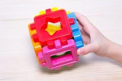 Zamyka up child& x27; s wręcza bawić się z kolorowym plastikowym konstruktorem na drewnianym tle Obraz Royalty Free