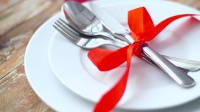 Zamyka up cutlery wiążący z czerwonym faborkiem na talerzu zbiory